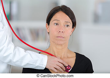 female doctor examining the patient with stethoscope