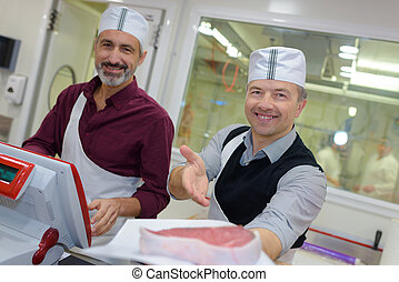 Two male butchers showing off their meat