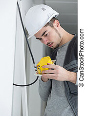handsome young electrician working at construction site