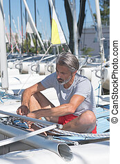 attractive sailor rigging hobbie-cat before sailing course