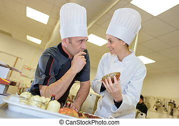 three professional chefs working in commercial kitchen