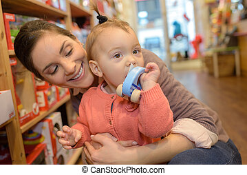 smiling mother embracing daughter in store
