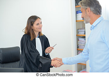 Female magistrate shaking hands with man