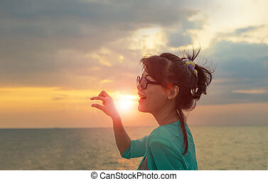 head shot of beautiful asian younger woman and hand acting against sun set sky at sea beach happiness emotion