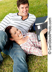 Couple of happy students using a laptop lying on the grass...