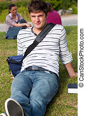 Handsome male student lying on the grass with his schoolbag