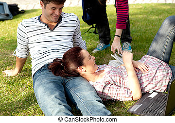 Couple of bright students lying on the grass at their campus...