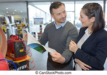 Couple looking at specifications book for power pack