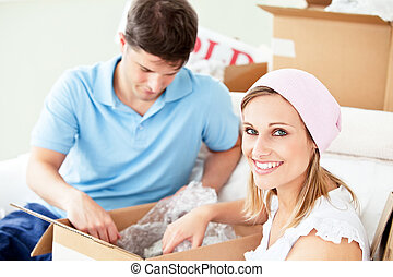 Ambitious young couple unpacking boxes with glasses in their...