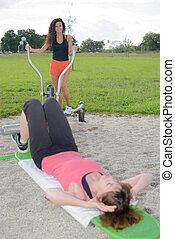 Women using exercise equipment in park