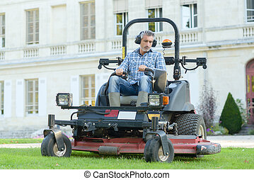 Man mowing lawn at manor house