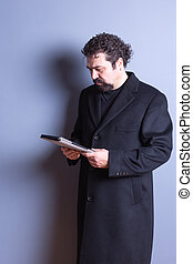 Man Wearing Trench Coat Reading from Tablet - Three Quarter...