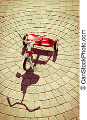 Red Tricycle with Shadow on Sunny Stone Patio - High Angle...