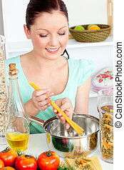 Charming woman cooking sphaghetti in the kitchen at home