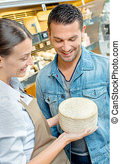 Shop assistant holding cheese, showing customer