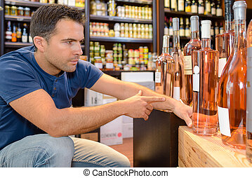 handsome young man choosing fine wines