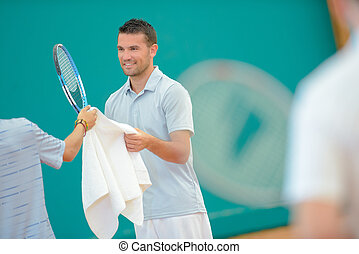Tennis player accepting towel