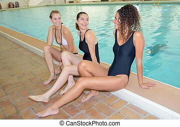 Three ladies sat on side of indoor pool
