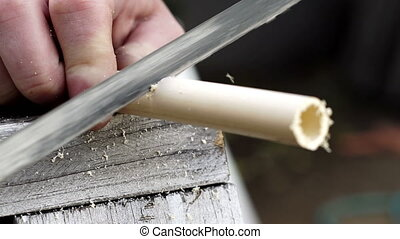PVC Pipe Cutting Close Up - Close up shot of a person...