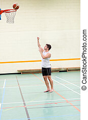 Good-looking man playing basketball in a gymnasium