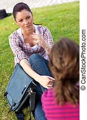 Two female friends talking together sitting on the grass at...