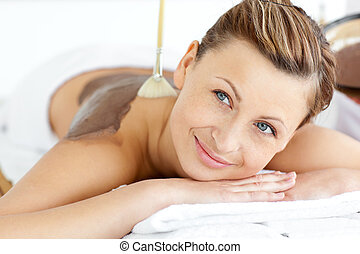 Relaxed young woman enjoying a beauty treatment with mud in...
