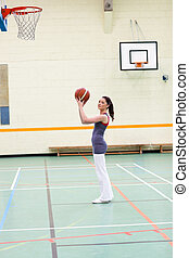 Concentrated woman practicing basketball in a gymnasium