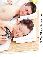 Lovely young couple receiving a back massage with hot stones