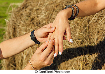 Man putting engagement ring on woman's hand outdoors.