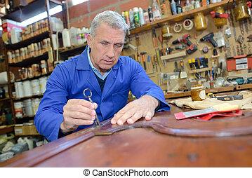 older man restoring a table