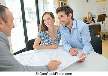 Architect drawing up plans with young couple