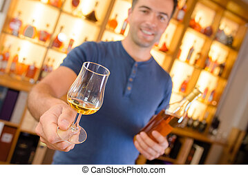 Man holding forward a glass of brandy