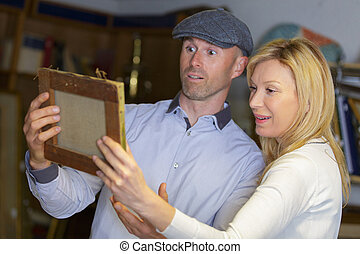 cheerful couple looking at creative picture in art gallery