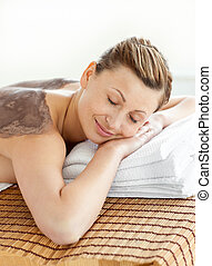 Merry caucasian woman lying on a massage table with mud on...