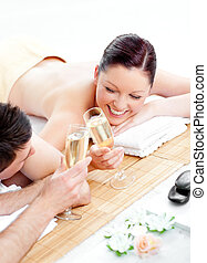 Loving young couple drinking champagne lying on a massage...