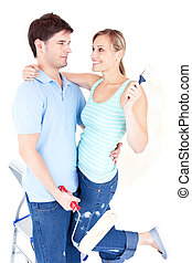 Affectionate young couple painting a room