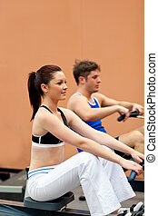 Athletic people using a rower in a fitness center