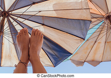 Young girl's feet up on the beach umbrella background