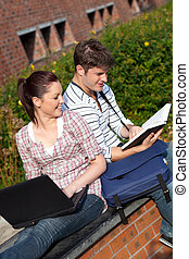 Young couple reading a book sitting - Young couple reqding a...