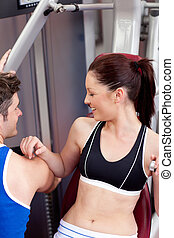 Cute athletic woman using a bench press with her coach in a...