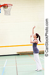 Gifted woman practicing basketball in a gymnasium