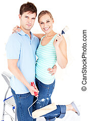 Loving caucasian couple painting a room