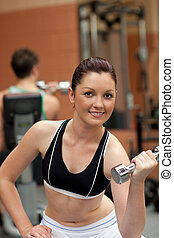 Portrait of an attractive woman working out with dumbbells...