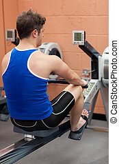 Athletic caucasian man using a rower in a fitness center