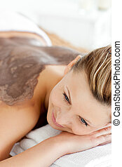 relaxed woman receiving a mud treatment in a spa center