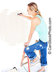 Animated young woman painting a room in her new house