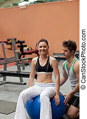 Woman sitting on a musculation ball with her personnal coach...