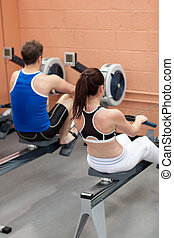 Sportsmen using a rower in a fitness center