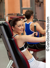 couple using a bench press and woman looking at the camera...