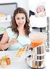 Caring mother preparing food for her lovely baby in the...